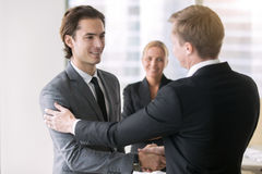 Two businessmen handshaking. Boss promoting young subordinate. Two businessmen handshaking, congratulating on promotion, ensure long-term prosperity, human stock images