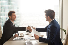 Two businessmen handshaking over office desk, making deal, accep. Two satisfied businessmen shaking hands at office desk after successful negotiations, business Royalty Free Stock Photos
