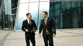 Two businessmen have a break. Two young successful businessmen easy communicating and discussing about something fun outdoor. Midday break. Tablet PC in hand stock footage