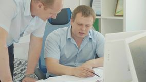 Two businessmen have a discussion and working with documents in the office.  stock footage