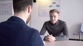 Two businessmen are having business negotiations in modern office. Young successful men are sitting at the wooden desk and the male professional in grey jumper stock video footage