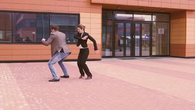 Two businessmen are having fun and laughing dancing near the modern business center. Man and woman celebrate success.  stock video footage
