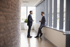 Two Businessmen Having Informal Meeting In Office Corridor Royalty Free Stock Images