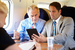 Two Businessmen Having Meeting On Train Stock Photo