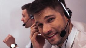 Two businessmen with headsets talking on voice call centre technical support stock footage