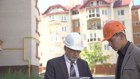 Two businessmen in helmet discussing scheme of building near builds. 4K stock video