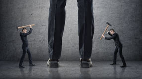 Two businessmen hitting giant legs of another with hammers on a concrete background Stock Photos