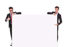 Two businessmen holding a big blank sign Stock Images
