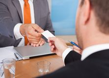 Two businessmen holding card over desk Royalty Free Stock Photos