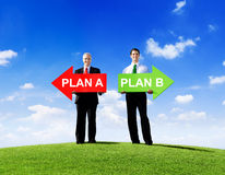 Two Businessmen Holding Contrasting Arrows Royalty Free Stock Photos