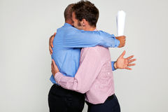 Two businessmen hugging Stock Photos