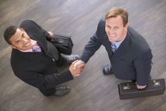 Two businessmen indoors shaking hands smiling Royalty Free Stock Photo