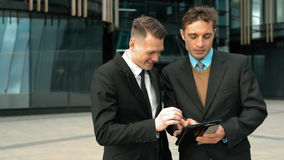 Two businessmen interecting discussion. Two young successful businessmen have interecting discussion using and working with tablet PC. Sliding, zooming, scaling stock footage