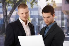 Two businessmen with laptop outside of office. Two businessmen standing with laptop computer outside of office, looking at screen, smiling Royalty Free Stock Images
