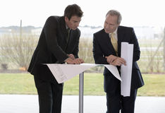 Two businessmen looking at blueprints in an office building Royalty Free Stock Photography