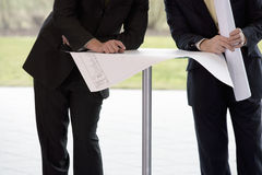 Two businessmen looking at blueprints in an office building Royalty Free Stock Photos