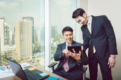 Two businessmen looking at digital tablet royalty free stock image