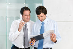 Two businessmen looking at documents Stock Image