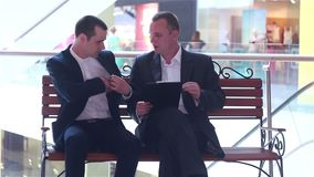Two businessmen looking documents and sign a contract. Two businessmen sitting on the bench looking documents and sign a contract stock video footage
