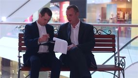 Two businessmen looking documents and sign a contract. Two businessmen sitting on the bench looking documents and sign a contract stock video