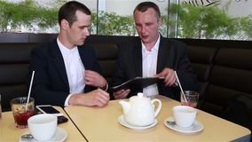 Two businessmen looking documents and sign a contract. Two businessmen sitting in a cafe and looking documents and sign a contract stock video footage