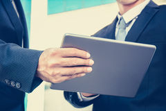 Two businessmen looking at tablet pc, vintage tone Royalty Free Stock Photos