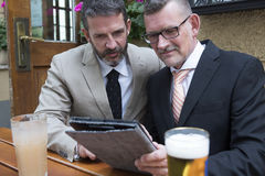 Two businessmen looking at a tablet Royalty Free Stock Image