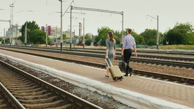 Two businessmen with luggage go along the railroad. Business travel partner. REar view stock footage