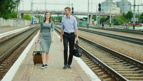 Two businessmen with luggage go along the railroad. Business travel partner stock video