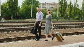 Two businessmen with luggage go along the railroad. Business travel partner stock footage