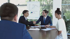 Two businessmen made a successful deal and shakes hands. Two businessmen are sitting in the office at the conference. Two business people are making a successful stock footage