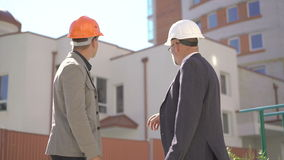 Two businessmen meet and shake hands near busy modern office building. 4K stock footage