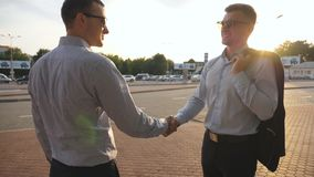 Two businessmen meeting at city street and greeting each other. Business handshake outdoor. Shaking of male arms outside. Colleagues meet and shake hands in stock video