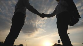 Two businessmen meeting and greeting each other in urban environment. Business handshake outdoor. Shaking of male arms. Outside. Colleagues shake hands in the stock footage