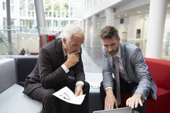 Two Businessmen Meeting In Lobby Area Of Modern Office Royalty Free Stock Images