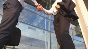 Two businessmen meeting near office building and greeting each other. Business handshake outdoor in urban environment. Shaking of male arms outside. Colleagues stock footage