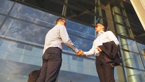 Two businessmen meeting near office and greeting each other. Colleagues shake hands in the urban environment. Business. Handshake outdoor. Shaking of male arms stock footage