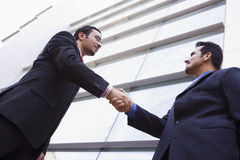 Two businessmen meeting outside office building. Two businessmen meeting outside modern office building Stock Photo