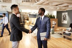 Two Businessmen Meeting And Shaking Hands In Modern Open Plan Office royalty free stock image