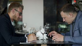 Two businessmen meets for discussion questions in their lunch in the cafe. Two businessmen meets for discussion questions in their lunch in the cafe . Handsome stock footage