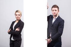 Two businessmen: a man and a woman are standing on either side o Royalty Free Stock Photography