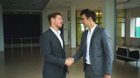 Two businessmen met in the office and shake hands. Two businessman shake hands in office stock footage