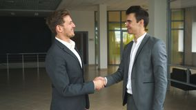 Two businessmen met in the office and shake hands. Two businessman shake hands in office stock video footage