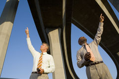 Two businessmen with mobile phones beneath overpasses, pointing upwards, low angle view Stock Image
