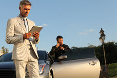 Two Businessmen Near Luxury Car, iPad and Cell Pho. Two businessmen near luxury car looking at iPad and talking on cell phone, suits and ties, with some park in Stock Images