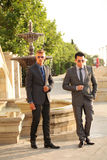 Two Businessmen Near Water Fountain, Sunglasses. Two businessmen near a water fountain, sunglasses, suits and ties Royalty Free Stock Images