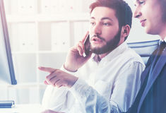 Two businessmen in office on a cell phone Stock Photo