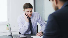Two businessmen in the office, one of them is talking on the mobile. Young businessman in the office 064 stock footage