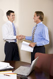Two businessmen in office shaking hands Stock Photos