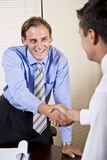Two businessmen in office shaking hands Stock Image